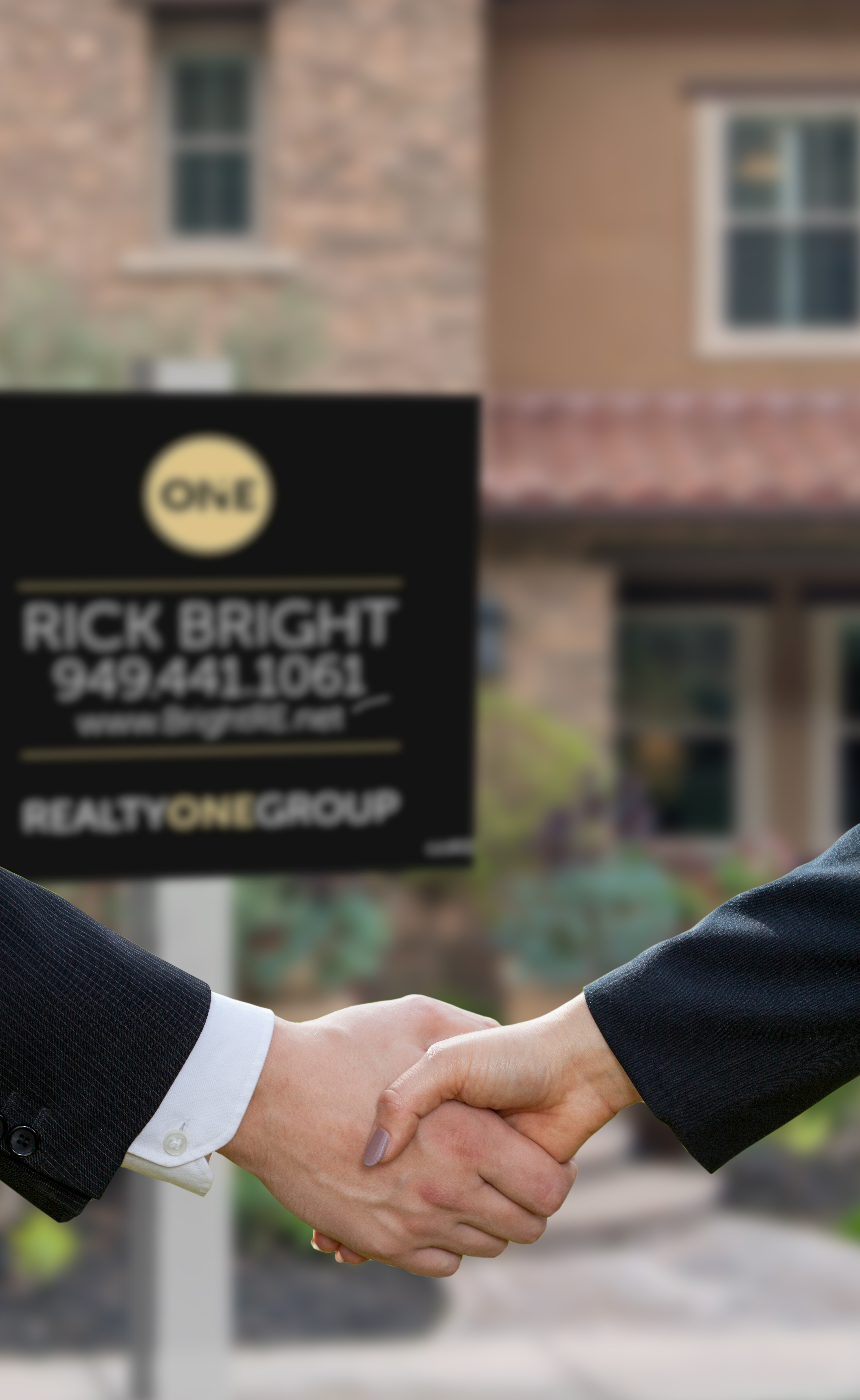 people shaking hands in front of real estate sign